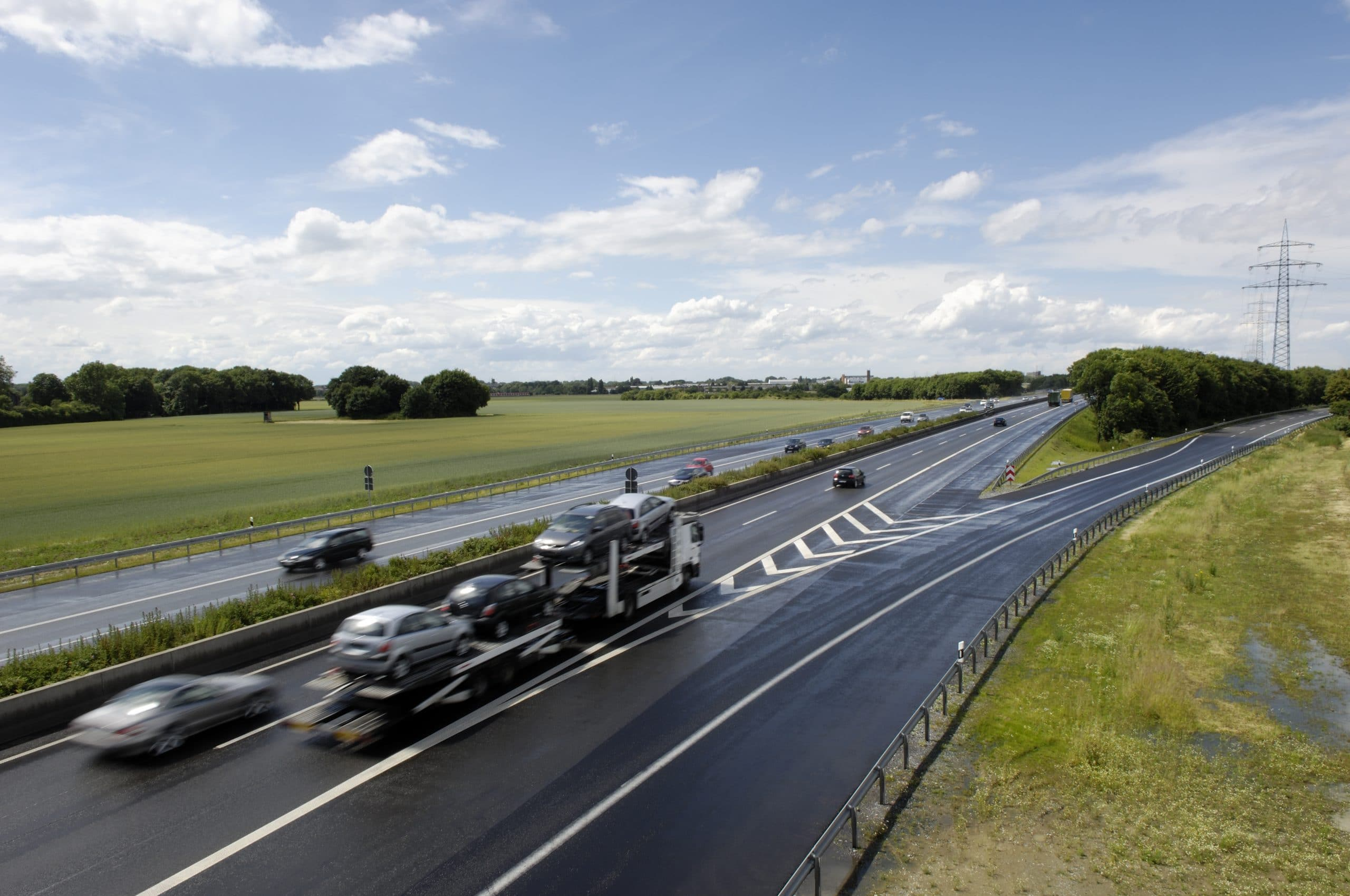 German highway with car-transporter and some other private cars.