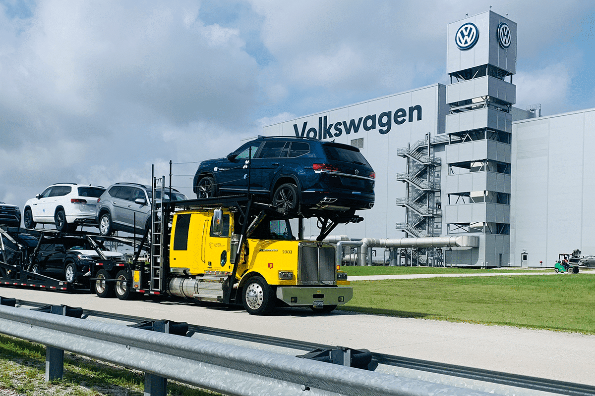 LOADED CAR CARRIER SITTING STILL IN FRONT OF VOLKSWAGEN PLANT